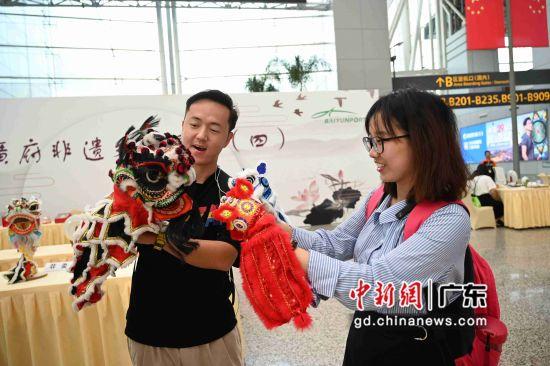 机场旅客和黎家狮传人举着狮头合影留念。