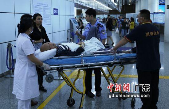 皇岗边检民警协助医护人员护送患者至桥头。(摄影:黄俊生)