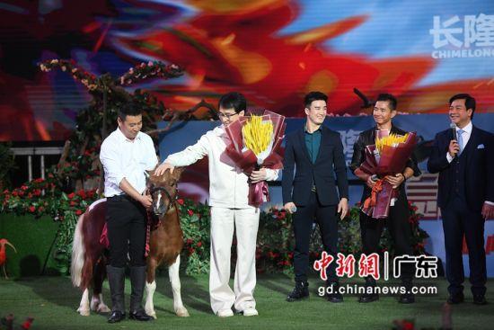"""主办方牵着一匹马向《急先锋》主创送上大麦,寓意""""马上大卖""""。 ( 姬东摄影)"""