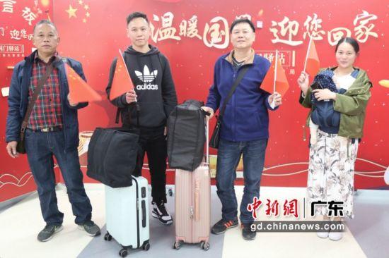 """旅客在""""温暖国门 迎您回家""""为背景的""""国门驿站""""前合影 摄影:吴一木"""