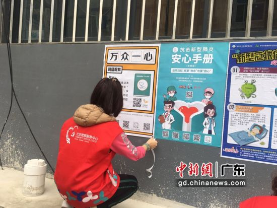 工作人员在社区内粘贴海报。(摄影:钟欣)