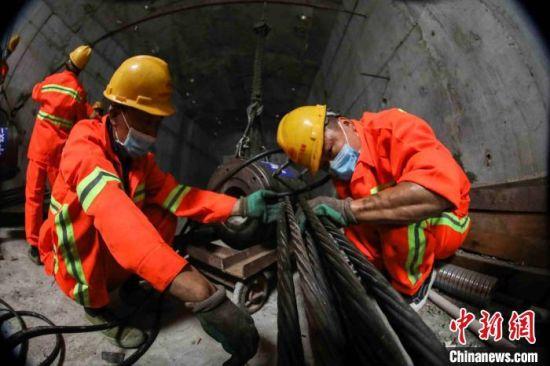 施工人员安装锚具开展张拉作业 邓联旭 摄