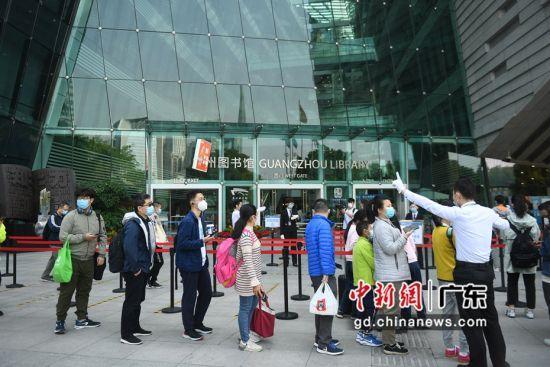 读者在广州图书馆外排队测温后进入。(姬东摄影)