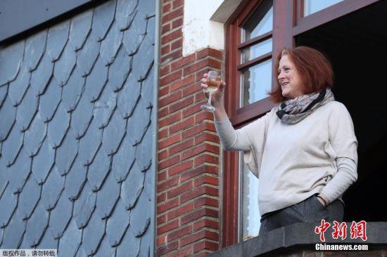 """当地时间3月22日,比利时首都布鲁塞尔安德莱赫特镇,在当地政府实施封锁期间,居民们在""""安全距离""""的前提下颇有仪式感的进行餐前敬酒。"""