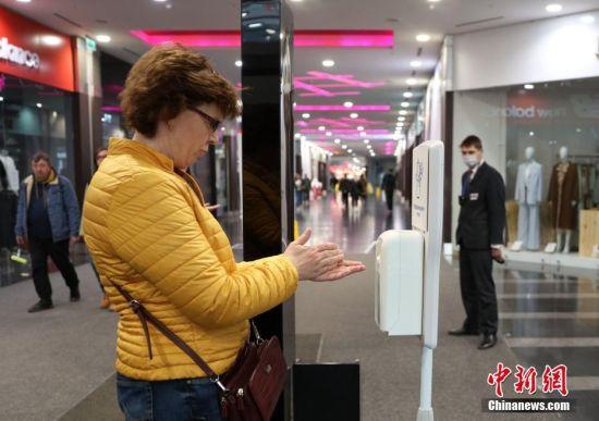 """当地时间3月28日,莫斯科进入""""准封城""""状态。莫斯科的""""卡比托利""""购物休闲中心关闭。顾客需要通过临时开出的一条通道进入中心里面的超市。图为在入口处,顾客在使用免洗洗手液。截至当日,全俄累计感染新冠病毒人数达到了1264人,其中817例出现在莫斯科。目前,莫斯科绝大多数公共场所已被陆续关闭。中新社记者 王修君 摄"""