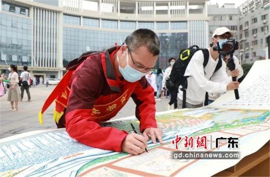 图为陈维生在一幅有惠州市援鄂医疗队75名队员签名的龙门农民画上签上自己的名字,至此该艺术作品76名队员签名圆满 惠州市第三人民医院供图