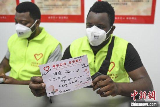 4月20日,广东省广州市白云区,同和街外籍友人青年志愿服务队队员展示慰问卡片。 中新社记者 陈骥�F 摄
