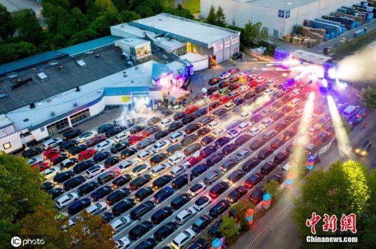 """近日,德国下萨克森州许托夫,几百辆汽车有序停放在一处空地上,现场俨然一个大型""""蹦迪""""现场。随着闪烁的灯光和劲爆的音乐,民众在自己的车里狂欢。据悉,为了维持生计,一家舞厅想出汽车迪斯科的办法,每天吸引大批人开车前往,感受这种新型迪斯科。图片来源:ICphoto"""