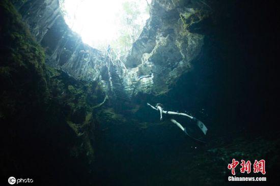 """5月22日消息,墨西哥尤卡坦半岛有许多""""天坑"""",是洞潜爱好者的天堂。41岁的摄影师Alex Voyer在尤卡坦半岛拍摄了一组洞潜大片,这组水下照片没有使用人工光源,画面中,Alex Voyer的女友Marianne Aventurier在天坑的洞穴潜水。扑朔迷离的幽暗光线,神秘的水下洞穴,怡然自得的潜水者,构成的画面十分唯美。Alex称他和女友正在环球世界,这里是最好的免费潜水胜地。图片来源:ICphoto"""