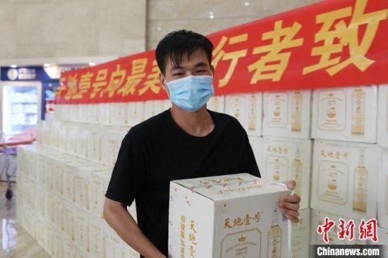 """热心公益的广州""""街坊""""林同猛正在搬饮料 立璞 摄"""