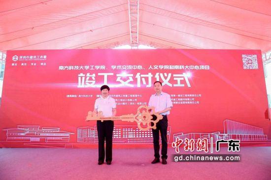 图为深圳市建筑工务署署长乔恒利(右)向南方科技大学党委书记郭雨蓉(左)移交钥匙牌。(中建三局一公司 供图)