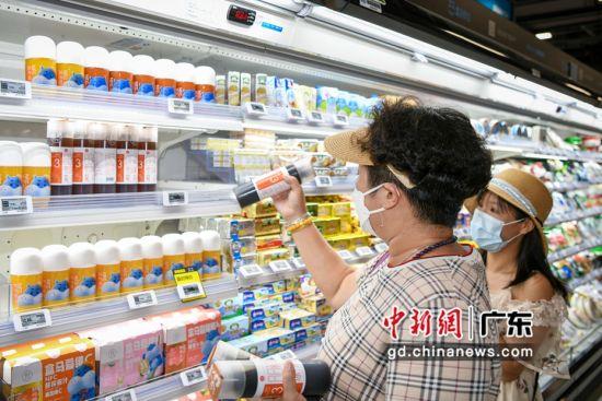 消费者在超市选购日日鲜凉茶。钟欣 摄