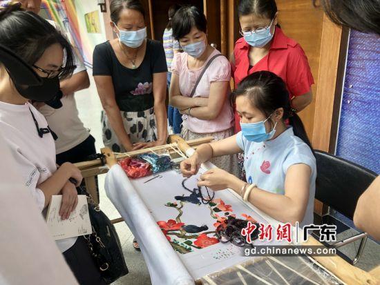 刺绣工艺大师梁淑萍对绣品进行专业讲解。 蔡伟英 摄