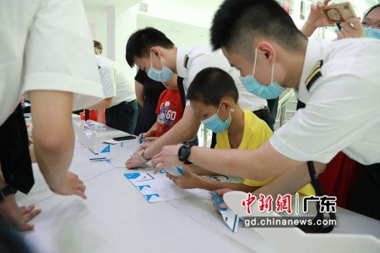 南航举办广东援鄂医护人员专场开放日活动。图为小朋友在家长的陪同下,跟着飞行员志愿者学习折纸飞机。。作者:南航航空供图