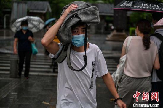 9月4日傍晚,广东省广州市天河区,一名行人用书包遮雨。当天,广州同时发布了暴雨预警与高温预警。 中新社记者 陈骥�F 摄