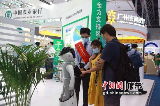 在农行展位前,智能机器人与参展客商积极互动。广东农行供图
