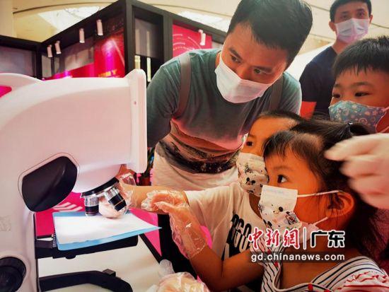 游客在参与病菌观察检测实验。广东科学中心 供图