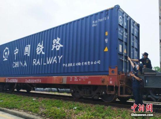图为5月19日,广州海关所属广州车站海关关员核对即将开行的中欧班列集装箱号。 中新社发 关悦 摄