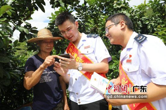 大埔税务人员向柚农推广电子税务局网上代开发票功能。大埔县税务局供图