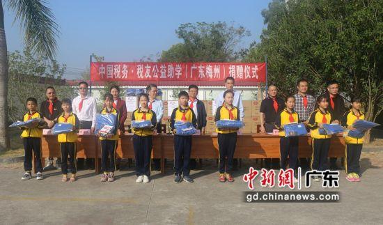 中国税务公益助学活动嘉宾给学生捐赠物资。温竹兰摄影