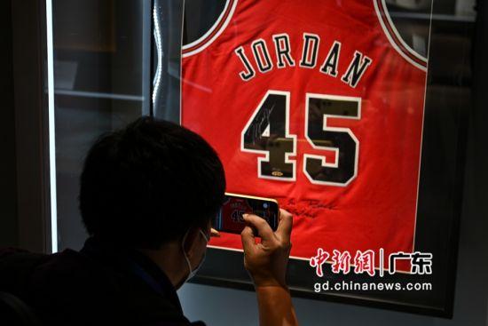 球迷在旗舰店内拍摄球星迈克尔・乔丹的签名球衣。陈骥�F 摄