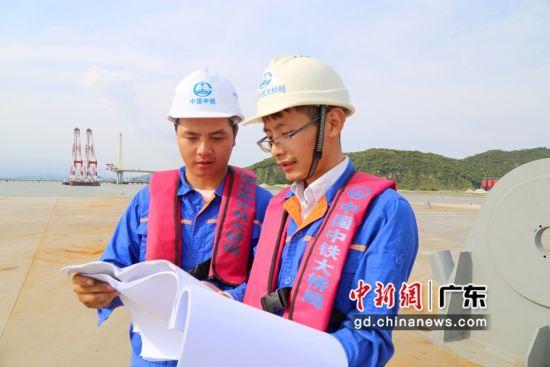 师傅江海明(右)拿着图纸给徒弟唐涛(左)详细讲解情景